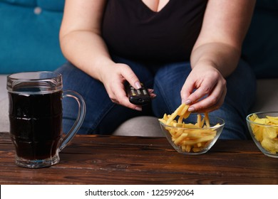 sedentary lifestyle, bad habits, food addiction, overeating, eating disorders. fat overweight woman sitting on the sofa with junk food and tv remote. depression, laziness problem eating