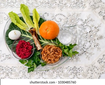 A seder plate for the Passover holiday featuring the symbolic elements on a white tablecloth with silver embellishments and with copy space