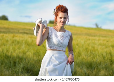 Sedlec, Czech Republic, July 1, 2019,  ginger hair bride with her shoes on the green field
