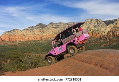 SEDONA, ARIZONA, UNITED STATES - DECEMBER 10, 2017: Pink Jeep Off Road Terrain Vehicle touring Broken Arrow Slick Rock with Tourists onboard