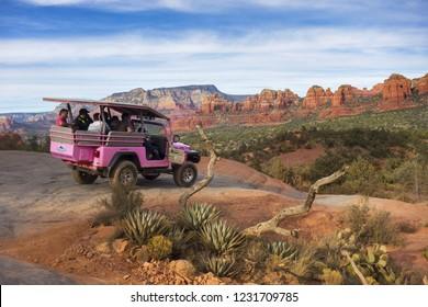 Sedona, Arizona, USA - December 10, 2017: Pink Jeep Off Road Terrain Vehicle with Tourists on Broken Arrow Slick Rock