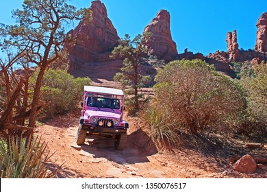Sedona, Arizona/USA - March 25 2019: a Pink Jeep descends the Broken Arrow trail leaving Chicken Point and heading back to Sedona