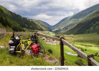 SEDRUN, SWITZERLAND - AUGUST 10: Bike with panniers parked by the road in Swiss Alps during an excursion in Sedrun, Switzerland on August 10, 2014.