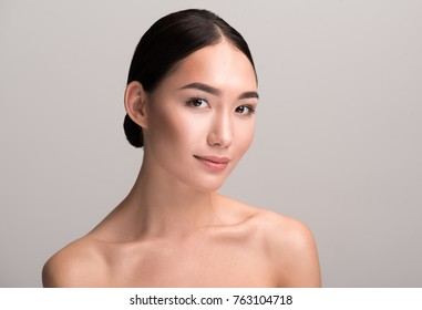 Seducing glance. Portrait of charming naked positive young asian woman is looking at camera with slight smile. She is demonstrating perfect and fresh skin. Isolated background