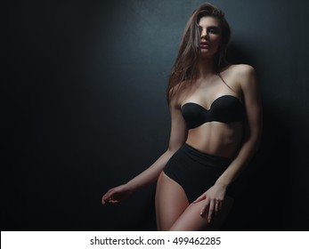 Seductive, beautiful and attractive young woman with loose brown hair and sexy gorgeous figure in the black seamless underwear and wool coat on the naked body is posing in the studio