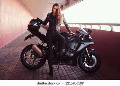 A seductive biker girl leaning on her superbike on a sidewalk inside the bridge.