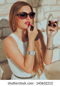 seductive blond woman sitting against a wall and doing make up .
