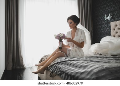 Seductive bride in silk robe sits on the grey bed in bright hotel room
