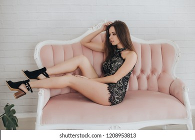 Seductive brunette girl in Bilje on a pink sofa