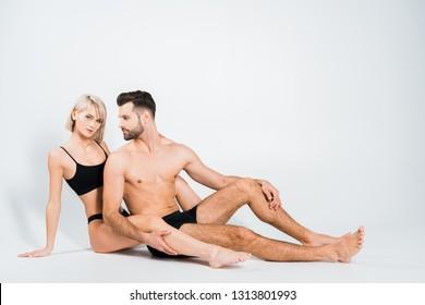 seductive couple in black underwear sitting isolated on grey