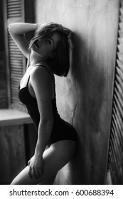 Seductive curvy woman in black teddy leans to the wall