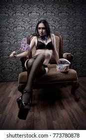 Seductive dark-haired girl sitting on armchair with heart