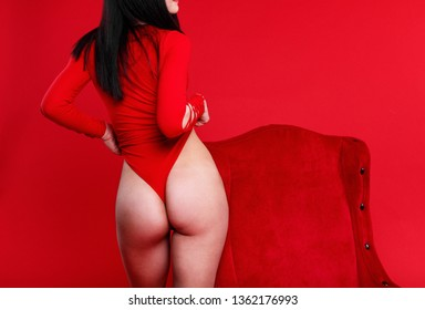 seductive female ass in red background slim girl legs and back in the red pylon seductive sexy dancer near the chair body of a young dancer in red  suit elastic buttocks of a young woman