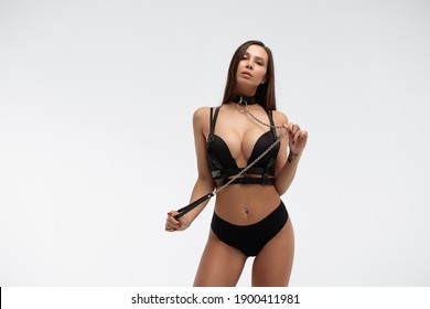 Seductive female in leather BDSM collar and black underwear standing on white background in studio and looking at camera