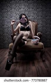 Seductive girl with heart in black underwear sitting on armchair