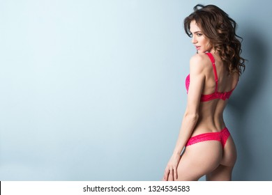 Seductive girl in pink underwear (lingerie) posing in the studio. Beauty and fashion.