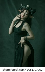Seductive horned girl with elvish ears posing over dark background