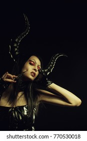 Seductive horned succubus with knife over dark background