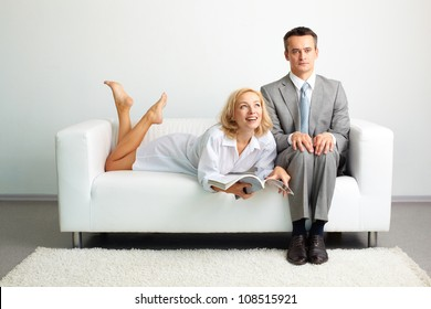 Seductive lady enjoying doing nothing lying on the sofa next to a serious businessman