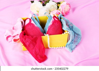 Seductive lingerie in present box on bed close-up
