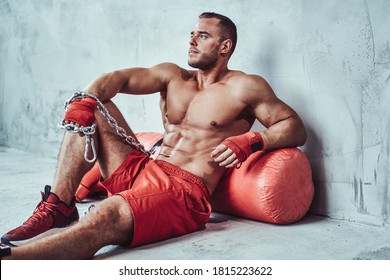 Seductive male sportsman with muscular bandaged hands and with chains sitting on floor leaning on punching bag.