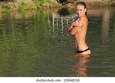 Seductive naked girl in the lake with wet hair
