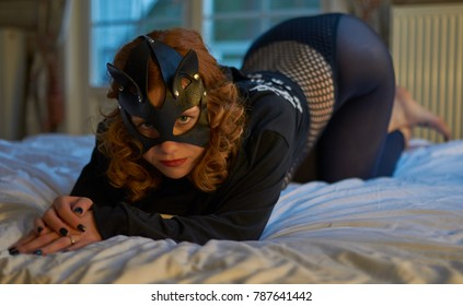Seductive playful cat-woman in sexy costume lying on bed