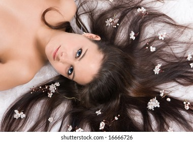 Seductive portrait of a beautiful young woman with spring blossoms in her hair
