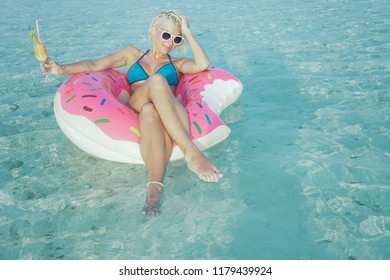 Seductive and sensuality woman is floating in inflatable doughnut in ocean. In right hand she is holding orange cocktail with straw in it. She is wearing white sunglasses and blue bikini.