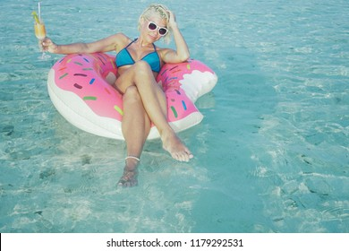 Seductive and sensuality woman is floating in rubber in ocean. In one hand she is holding orange cocktail. She is wearing white sunglasses and blue bikini. She is suntanning on warm sunny summer day.