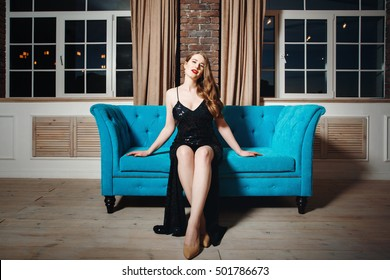 Seductive sexy model posing in loft interior in black dress. Woman with red lips.