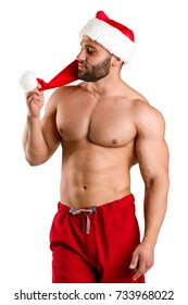 Seductive shirtless man in Christmas hat isolated on a white background. Christmas celebration concept.