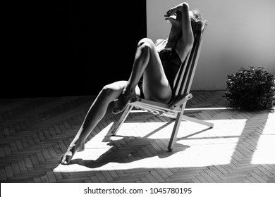 Seductive think woman with long legs poses in a lingerie in the rays of morning sun