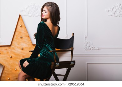 Seductive woman in casual velvet dress sitting on chair near big golden  star in modern studio on white wall.