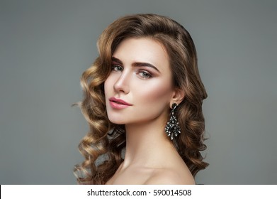 Seductive woman with curly hair on a gray background