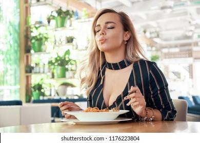 Seductive woman eating pasta, spaghetti closing eyes of pleasure. Gorgeous young blond woman having Italian food.