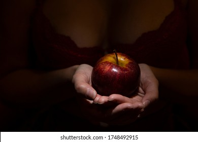 Seductive woman in lingerie with apple in hand