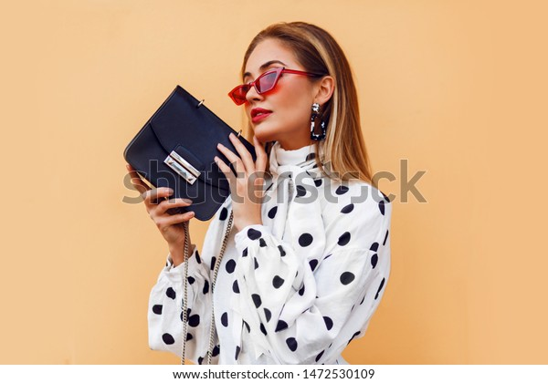 Seductive  woman in stylish   casual outfit posing with black leather luxury bag. Trendy accessories.  Red sunglasses. Modern hairstyle, bright makeup.