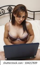 Seductive woman using her computer in the bedroom