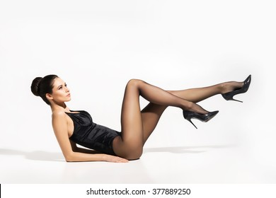 Seductive woman wearing pantyhose and heels with sexy legs up in the air over isolated background.