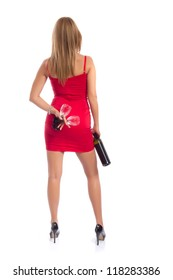 Seductive woman with wine - Attractive woman in a short red dress and high heel shoes holding a bottle of wine and two tall glasses, looking away from the camera, studio shot on white background