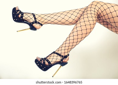Seductive woman's legs wearing fishnet stockings and high heels.