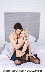 seductive young couple hugging while sitting on bed