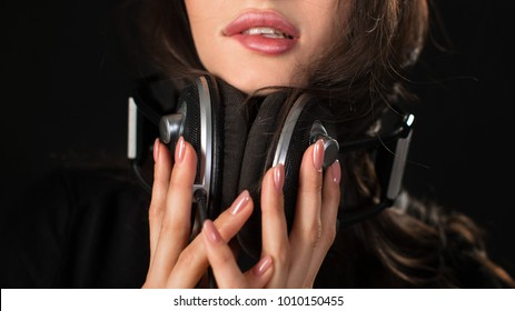 Seductive young female. dark background. Sexual mood. Female lips and hands with a headphones
