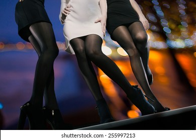 Seductive young ladies wearing short dresses, tights and high heels looking for adventures at night time. Girls having fun while wanna be picked up