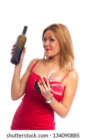 Seductive young lady in red dress holding a bottle of wine and tall wine glasses, smiling at the camera