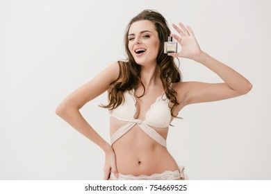 seductive young woman in white lace lingerie holding bottle of perfume and winking at camera isolated on grey