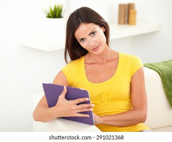 Seductive young woman in yellow tank top holding a tablet while looking at the camera