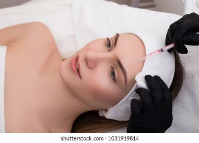 See after your skin! Attractive young girl getting a procedure of plasmolifting injection into the skin of her forehead.