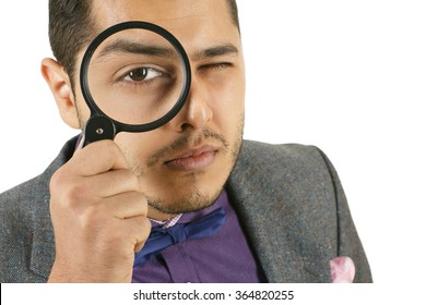 I see everything. Closeup studio portrait of a man looking to the camera through a magnifying glass